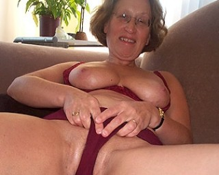 Granny with glasses masturbates pussy